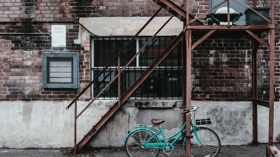 a-blue-bicycle-against-a-rusty-apartment-fire-escape